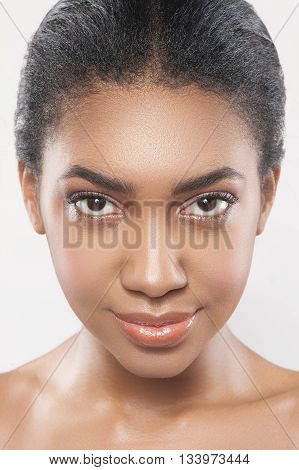 Portrait of attractive young mulatto woman looking forward with passion. She has perfect smooth skin. Isolated