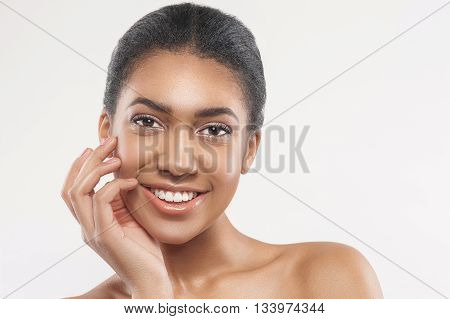 Portrait of pretty young african woman touching her smooth facial skin with enjoyment. She is standing with bare shoulders. The lady is smiling happily. Isolated