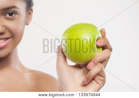 Close up of female hand holding a green apple. Young pretty african woman is standing and smiling. Isolated