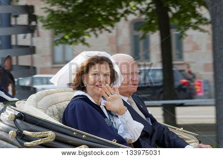 STOCKHOLM SWEDEN - JUN 06 2016: The swedish queen and king Silvia and Carl Gustaf Bernadotte waiving to the audience from the royal coach on their way to celebrate the swedish national day.