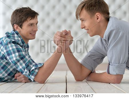 two men  at the table and armwrestling