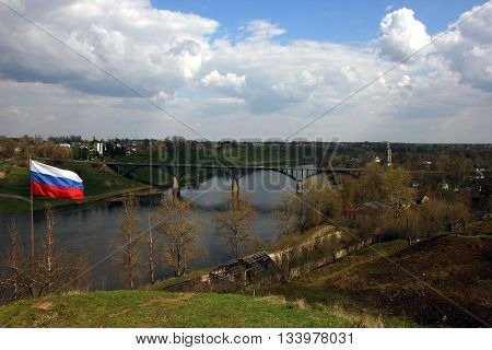 beautiful panoramic view from hill to old road bridge across the river and russian state flag on the hill Staritsa Russia