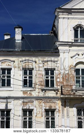 Fragment of vintage shabby old public building in classical style with peeling plaster