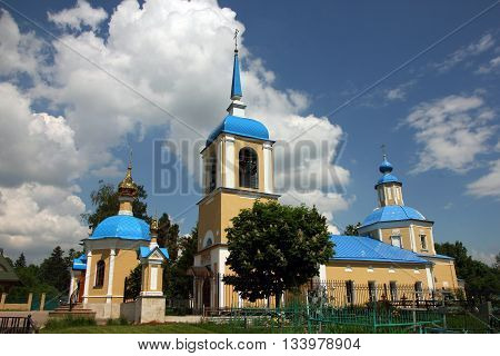 beautiful landscape with old russian orthodox church in classical style with yellow walls and blue roof and dome and belfry in village