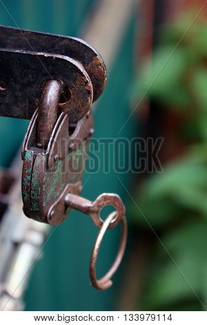 Old rusty metal green padlock with key on green metal gates closeup foreground