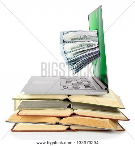 Stack of books and laptop with money from monitor screen isolated on white