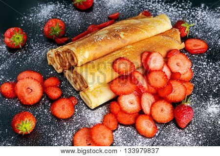 Sweet Rolled Pancakes powdered sugar with and strawberry