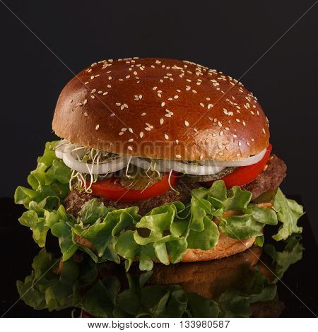 Juicy tasty burger with pickles tomatoes and onions on a black background