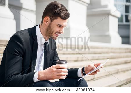Get some rest. Pleasant delighted smiling man sitting on the footsteps and holding papers while drinking coffee