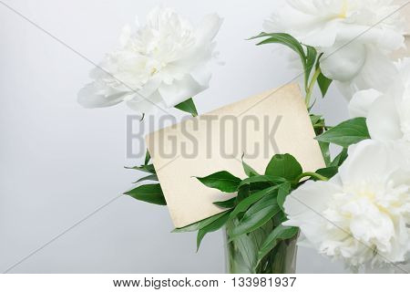 White peonies bouquet with retro blank card inside. Ready for your text.