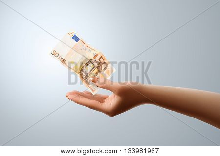 50 Euro flies to the female hand. Conceptual business image