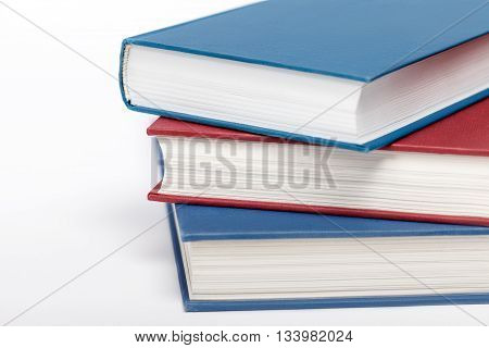 Three books on white background up close. Low aperture shot selective focus.
