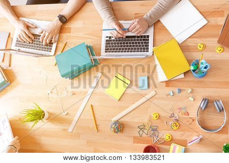 Business meeting. Top view of hands of guys working at office desk and using digital tablets, notebooks and various objects all around