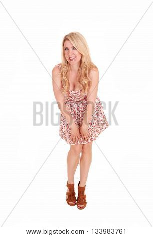 A lovely woman with long blond hair standing in a summer dress isolated for white background looking into the camera and bending forward.