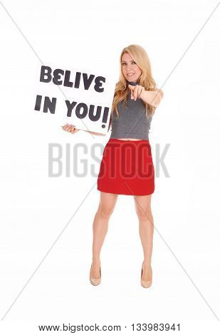 A lovely woman in a red skirt and gray sweater standing with a sign