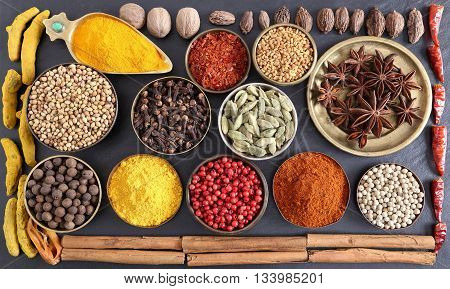 Colorful aromatic spices in bowls on the black ceramic background.