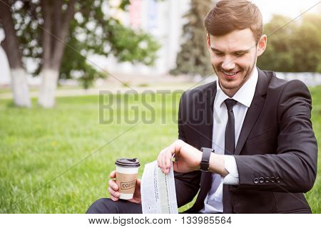 Glad to have rest. Cheerful handsome content man sitting on the grass and looking at his smart watch while drinking coffee