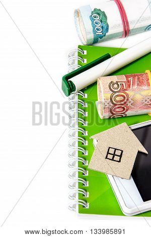 Paper house Russian money a pen and a notebook. Vertical edge