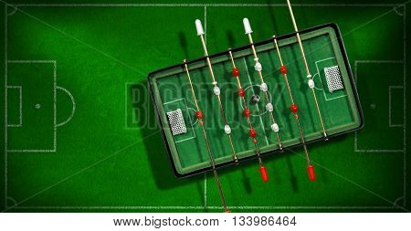 Top view of mini table football game with an old black and white soccer ball. On a green soccer field with shadows