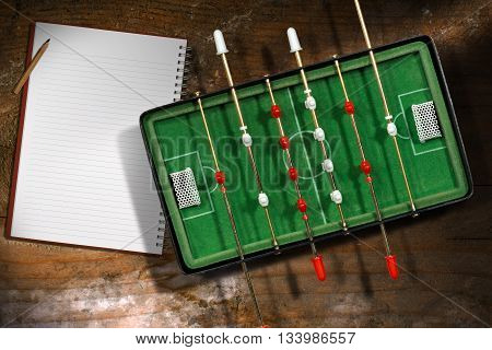 Top view of mini table football game with empty notebook and pencil. On a wooden table with shadows