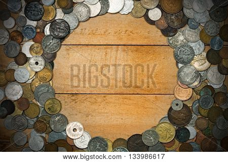 Old and vintage metallic coins on a wooden background with copy space. Round frame