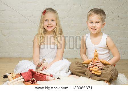 Smiling sibling children playing with stuffed animals
