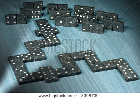 Close up of old wooden pieces of the domino game on a wooden table with shadows