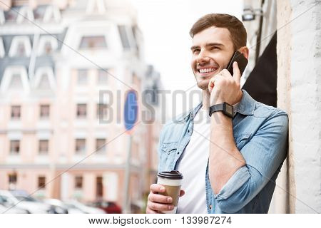 Talkative person. Cheerful delighted handsome man talking on cell phone and holding coffee while standing in the street