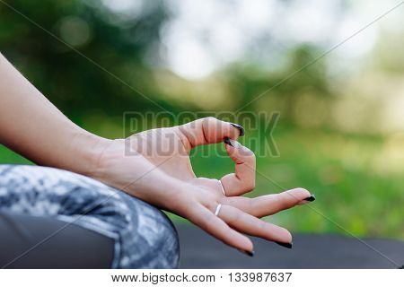 Young woman meditating indoors.A series of yoga poses. Closeup of woman's hands meditating indoors
