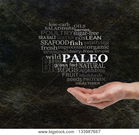 Consider The Paleo Diet - Chunky male hand with cupped palm  and a PALEO word cloud floating above on a dark stone cave wall effect background with copy space