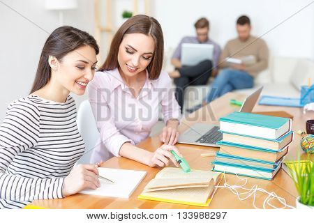It helps to study with friends. Two young girls reading book and making notes in notebook, studying together with guy in background