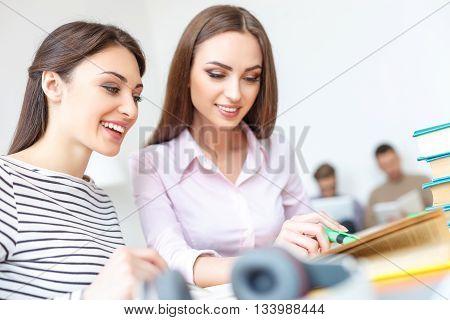 Helping out a classmate. Close up of two smiling girls deciding task, studying together for upcoming exams with guy in background