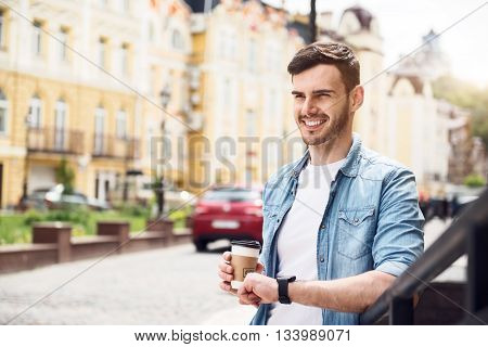 Life lover. Cheerful handsome smiling man drinking coffee and expressing joy while leaning on the handrail