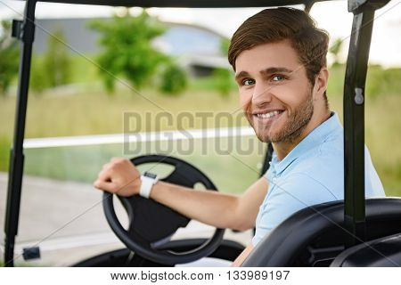 Golfer in golf cart. Close up of young happy male golfer driving golf cart and looking over shoulder