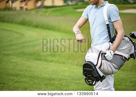 Very important not be late. Close up of golf player checking time on smartwatch while walking on beautiful golf course, carrying his bag