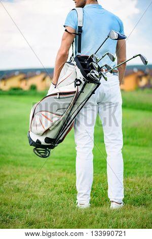 Ready to play. Close up of male golfer walking away while holding golf back, standing on green golf course