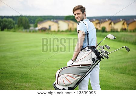 Day well spent. Smiling young guy walking away along green golf course, holding golf back and looking over his shoulder