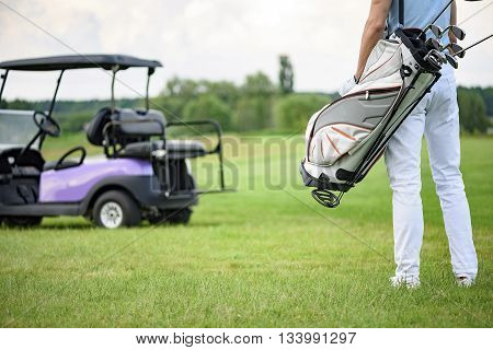 Ready to play golf. Close up of male golfer walking away holding golf back with golf cart on background