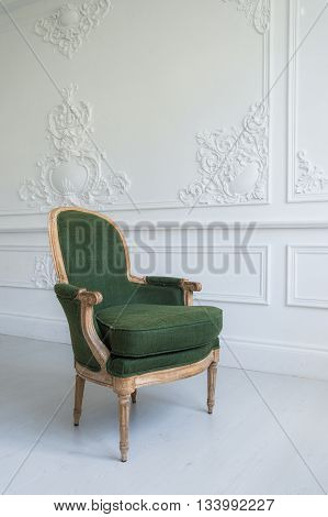 elegant green armchair in luxury clean bright white interior.
