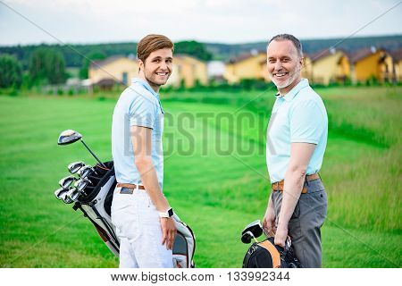 This how we like to spend our weekends. Partners on game standing on golf course, holding golf bags and smiling