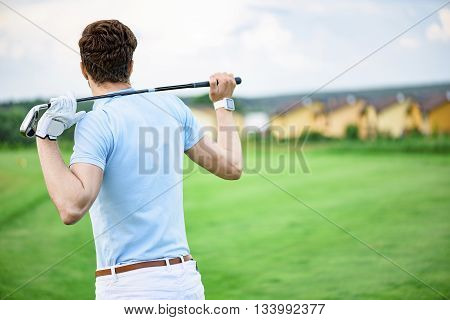 Master of the green. Man holding his golf club across his shoulders, tanding on golf course and watching golf course