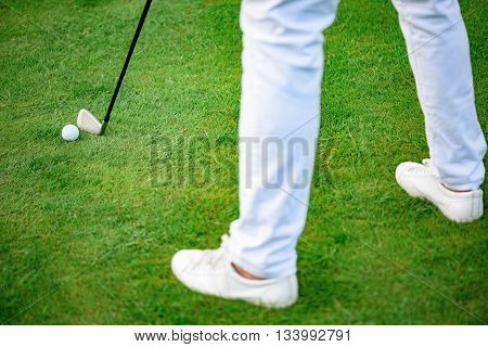 Grounding the club. Close up of golf player holding golf clud and going to make swing, standing on golf course