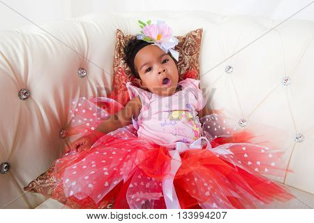 Little baby girl - in a beautiful dress lying and yawns