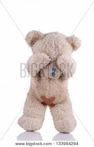 Toy bear with adhesive bandages on his private parts