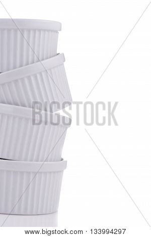 White ramekin dishes very unstable stack close-up isolated on white background
