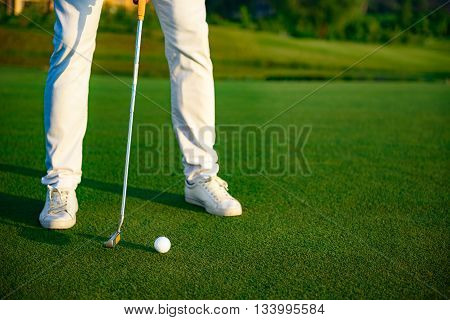 Practice makes perfect. Close-up of man playing golf while standing on green and going to shot