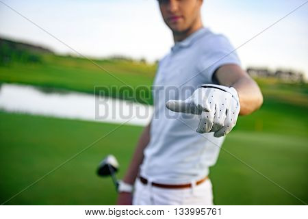 I waiting you on my team. Close up of finger pointing at camera by golfer finger, standing on green course and holding driver