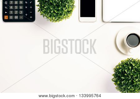 Topview of white office desktop with coffee cup plants calculator smartphone and closed laptop. Mock up