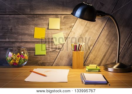 Closeup of creative designer desktop with lamp crumpled paper in glass bowl and stationery items on wooden wall background