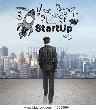 Start up concept with rocket ship sketch and businessman walking towards city on concrete ground